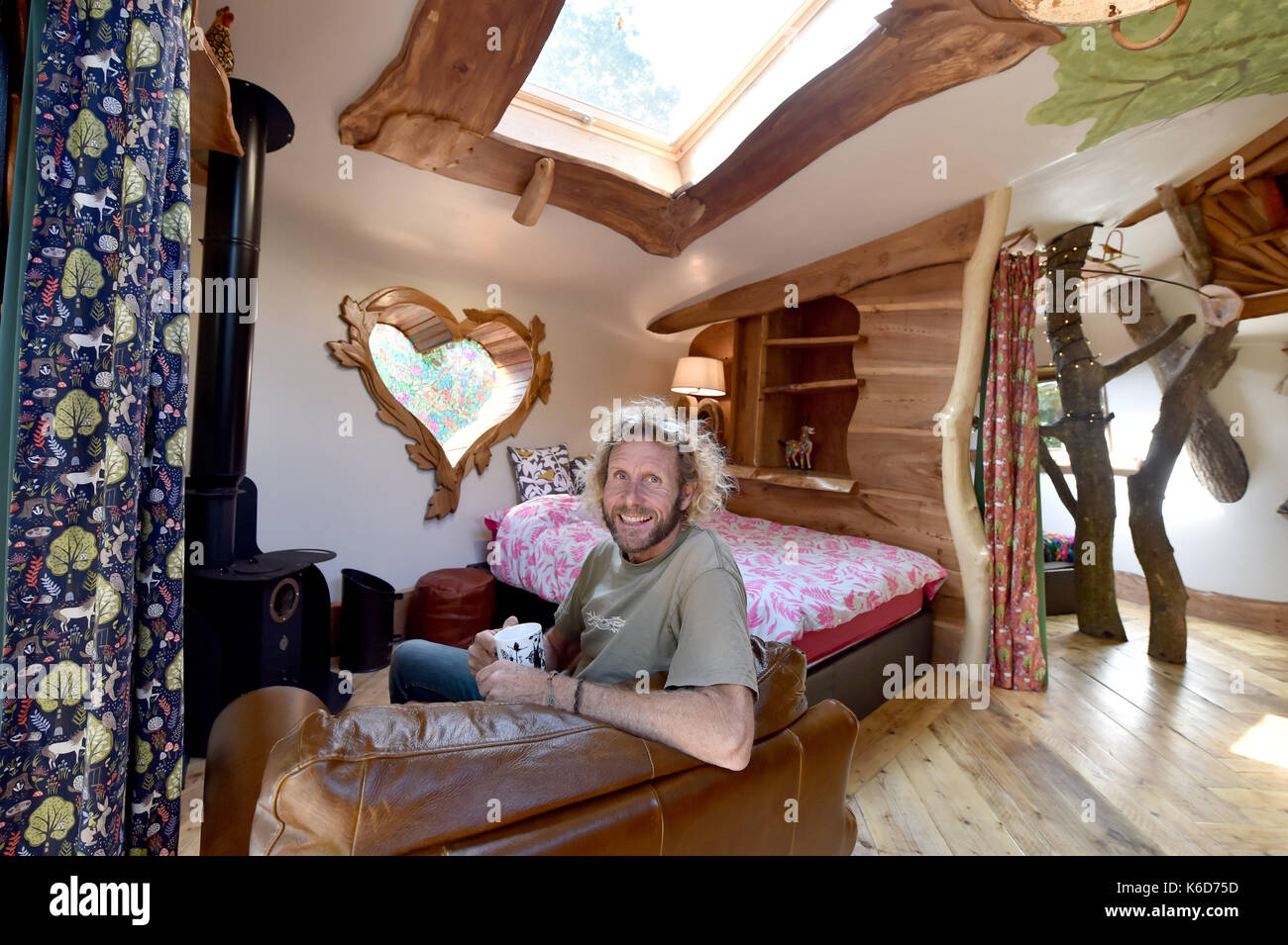 Ditchling Sussex, UK. 12th Sep, 2017. A new tree house has been unveiled at Blackberry Wood campsite near Ditchling in Sussex . The new upmarket tree house called Piggledy has been built by campsite owner Tim Johnson (pictured) and is larger than the original next door tree house called Higgledy . The quirky campsite is well known for having a London bus and an old Wessex helicopter where people can also stay in peaceful surroundings nestled just north of the South Downs National Park Credit: Simon Dack/Alamy Live News - Stock Image