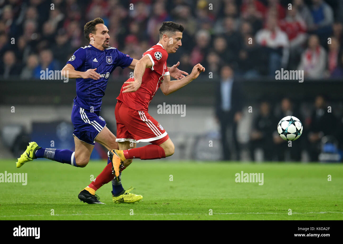 dpatop - Munich's Robert Lewandowski (r) is fouled by Anderlecht's Sven Kums during the Champions League Group B match between Bayern Munich's and RSC Anderlecht at the Allianz Arena in Munich, Germany, 12 September 2017. Photo: Tobias Hase/dpa - Stock Image
