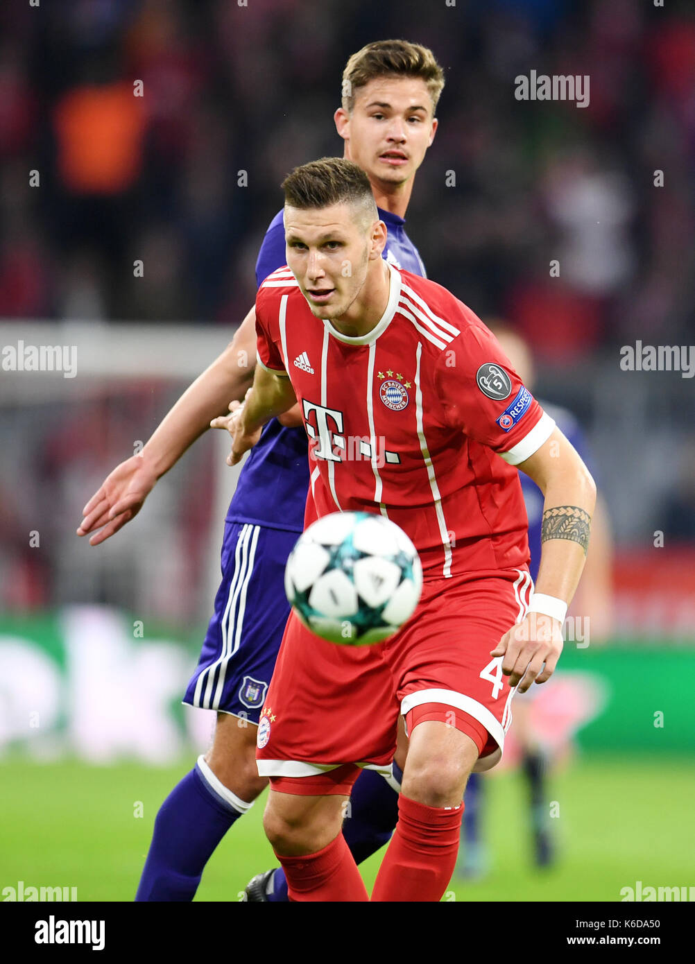 Munich's Niklas Suele (front) and Anderlecht's Olivier Deschacht in action during the Champions League Group B match between Bayern Munich's and RSC Anderlecht at the Allianz Arena in Munich, Germany, 12 September 2017. Photo: Tobias Hase/dpa - Stock Image