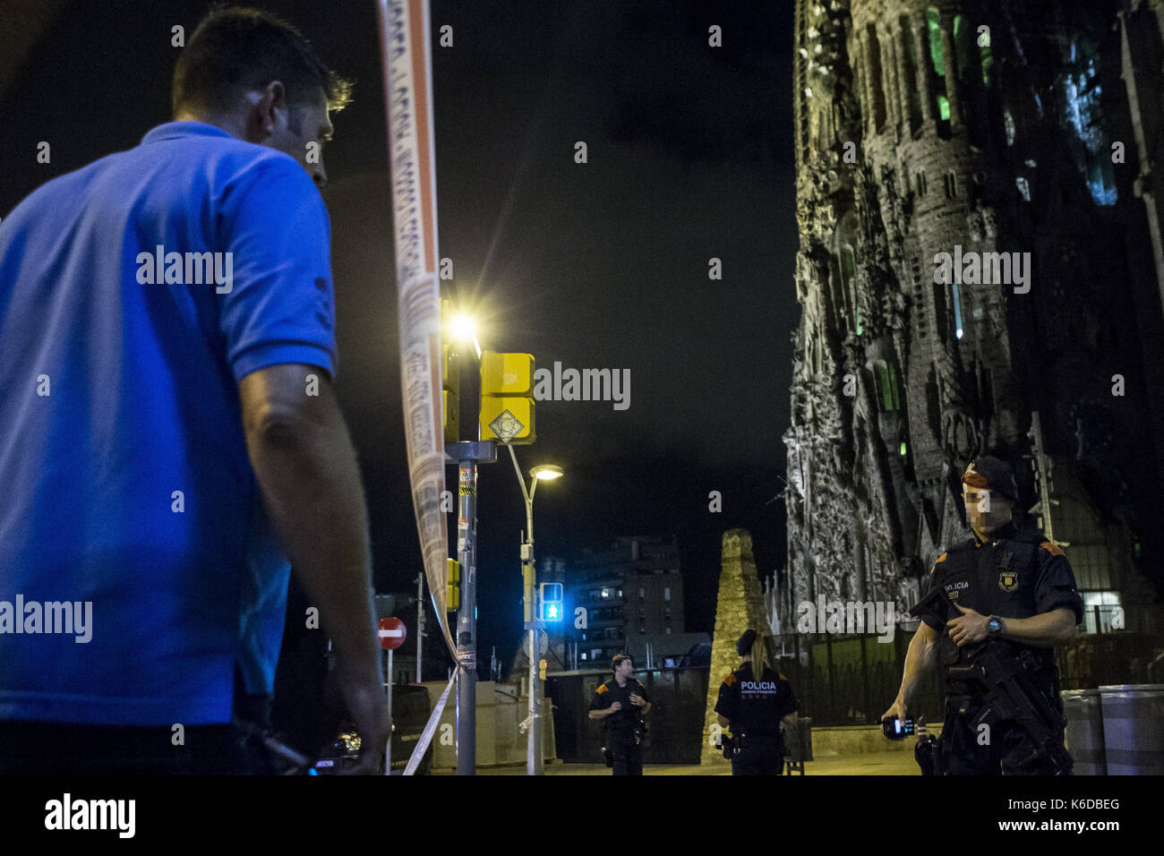 Members of the Mossos d'Esquadra, the Catalan Police, watch the perimeter of the Sagrada Familia after a terrorist - Stock Image