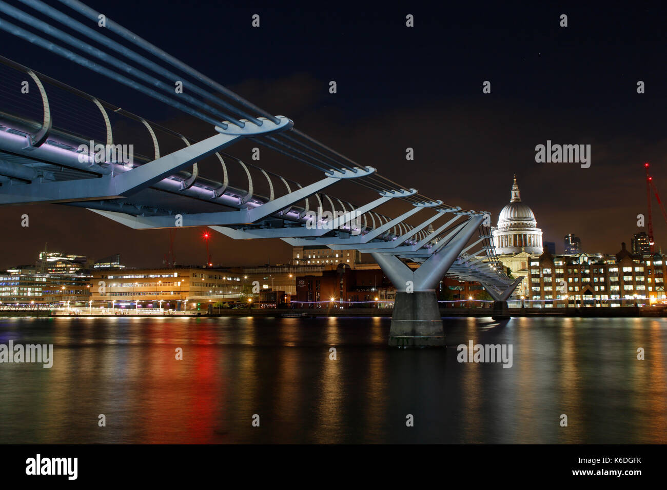 The Millennium Bridge at night with St Paul's Cathedral in the background. - Stock Image