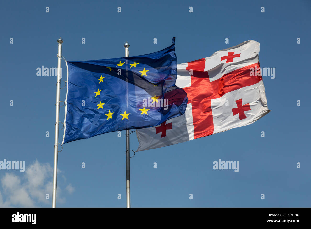 The flags of the European Union and Georgia flying side by side. - Stock Image