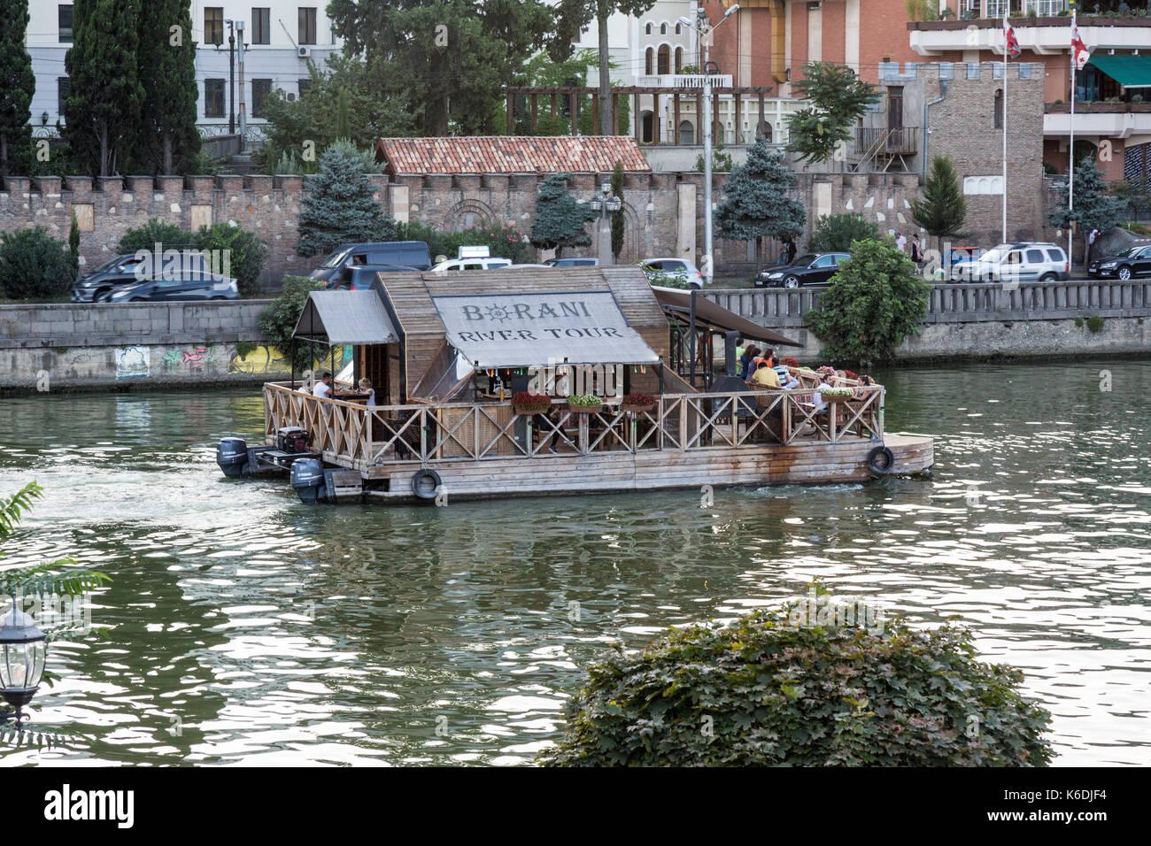 Tourist boat cruising on the Kura River in the centre of Tbilisi in Georgia. - Stock Image