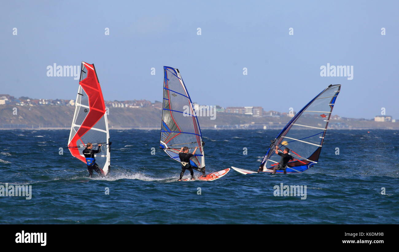 Enjoying the thrills of a fast ride, sail boarders under way in Poole Bay, Branksome UK - Stock Image