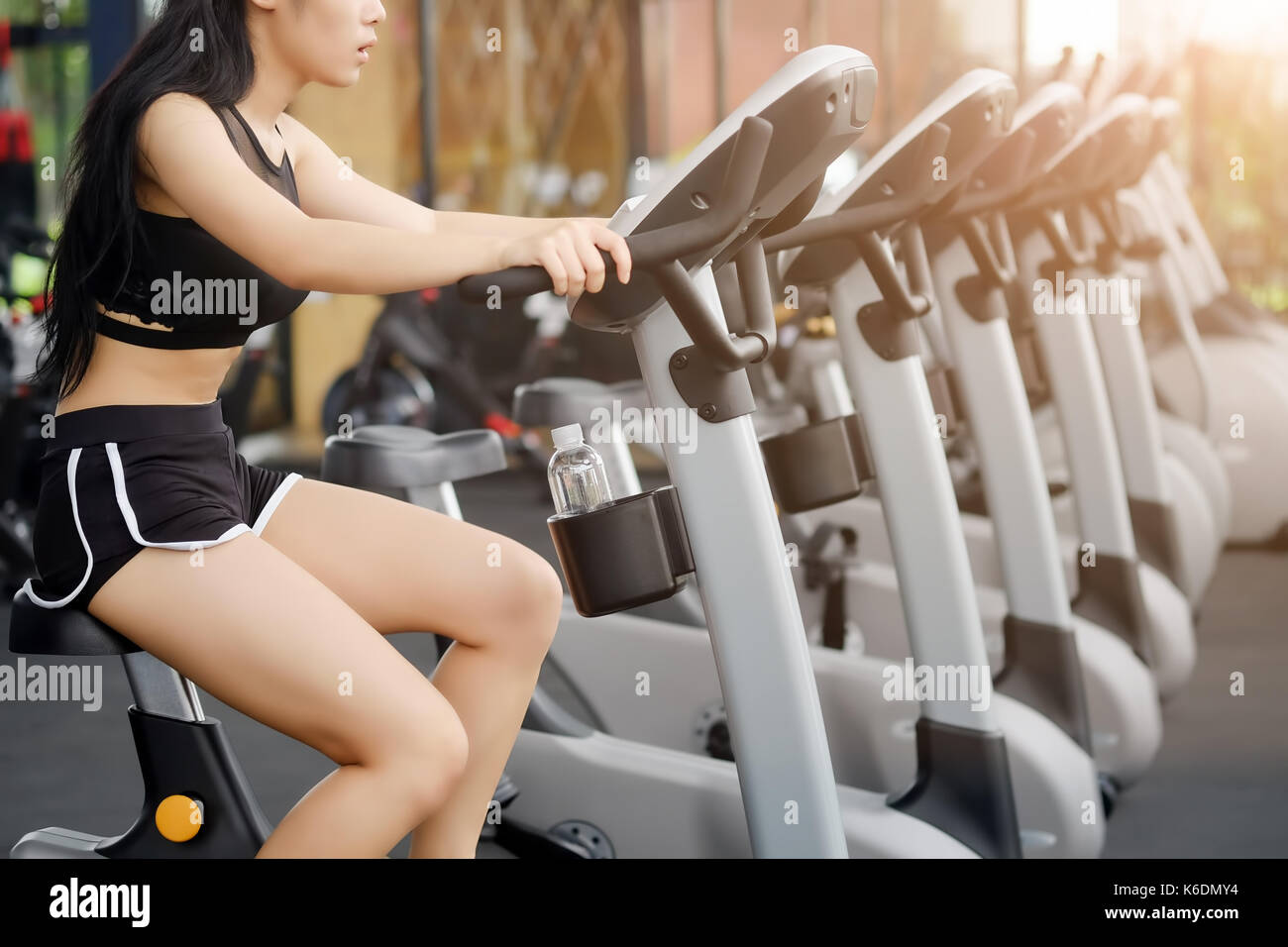 Sportive Woman during cycling workout in sport gym bike doing cardio exercise. - Stock Image