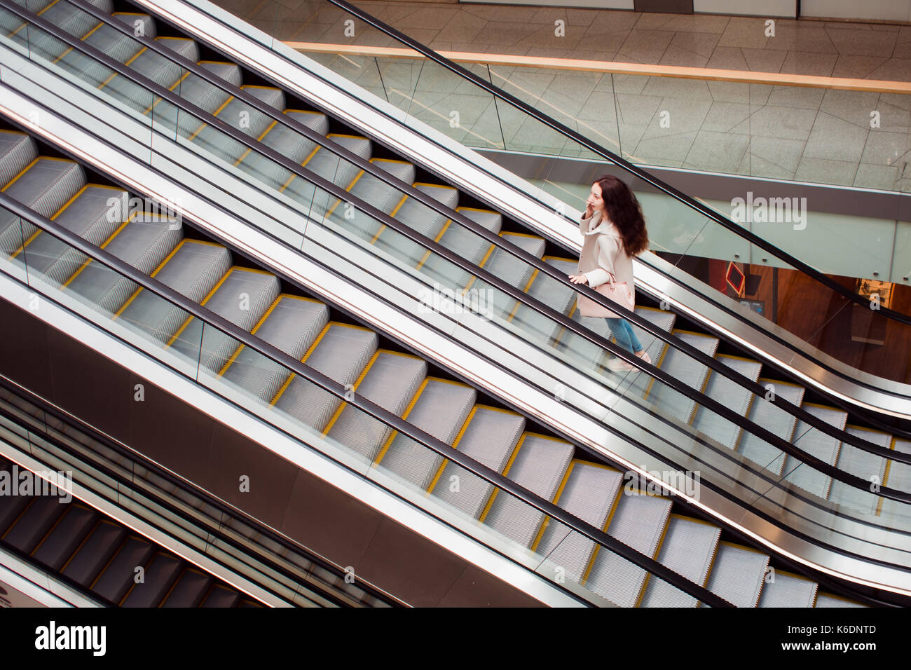 Young woman at the Mall rise up by escalator, view from the top - Stock Image