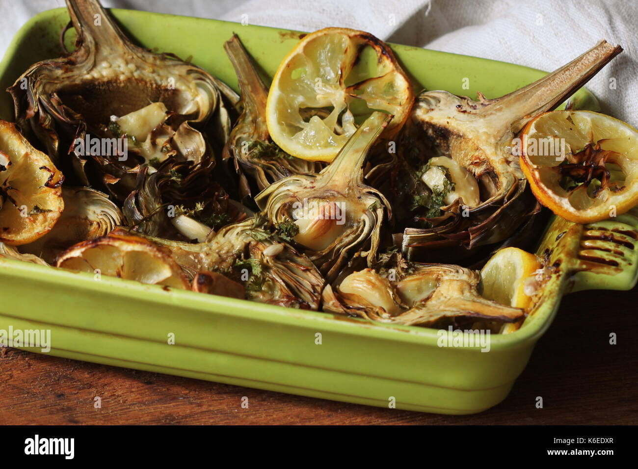 fried artichokes with garlic and lemon on pan - Stock Image