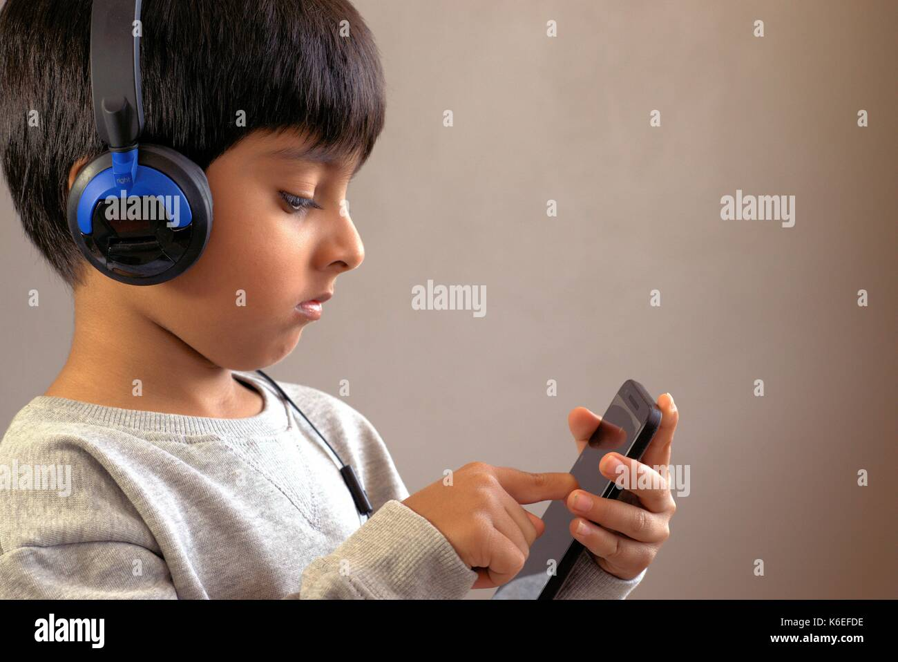 Child using smart phone. Kid wearing headphones looking at smartphone. Kid tapping on touchscreen. - Stock Image