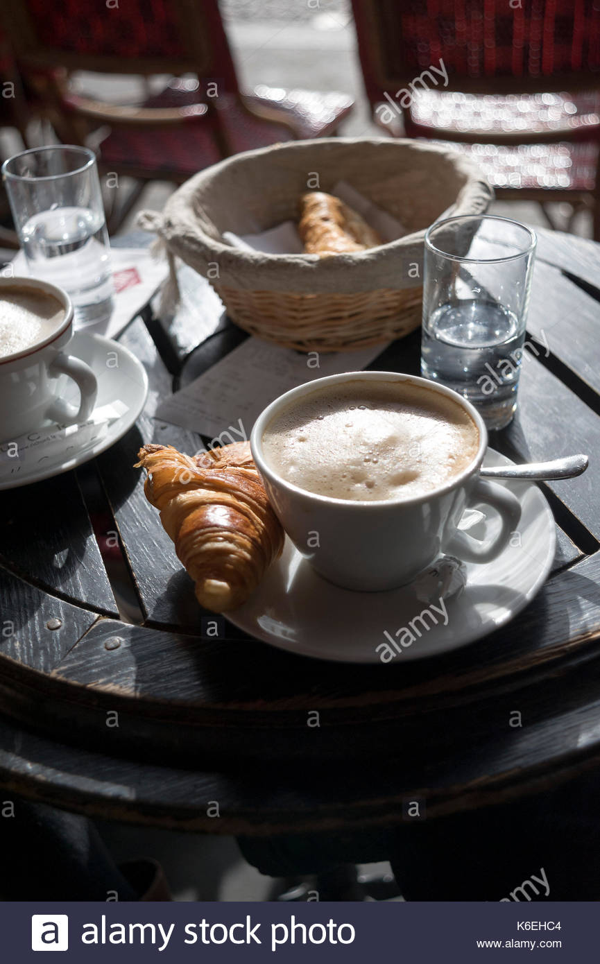 Outdoor table in a Parisian café in the morning light, detail, set for breakfast for 2, with 2 cups of coffee, 2 glasses of water and two croissants. - Stock Image