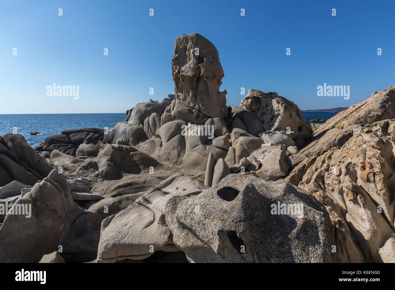 The sun shines on the rocks eroded by wind framing the blue sea Punta Molentis Villasimius Cagliari Sardinia Italy Europe - Stock Image
