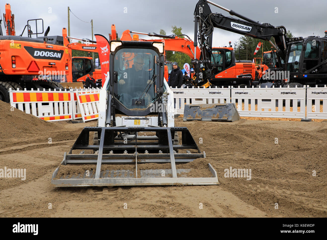 HYVINKAA, FINLAND - SEPTEMBER 8, 2017: Operator levels ground with Bobcat T450 Compact Track Loader and landplane attachment on sand work site on Maxp - Stock Image