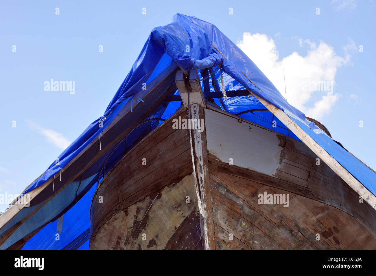 Bow of a Wooden Boat in dry dock and covered with a blue tarp - Stock Image