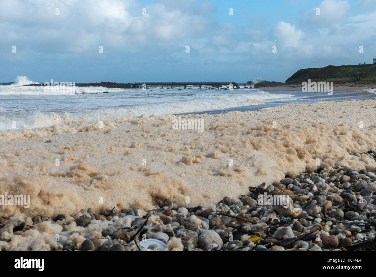 Cloudy skies, wild seascape and sea foam or spume washing up the pebble beach at Carrickmore Rd, Ballycastle, BT54, Northern Ireland,UK - Stock Image