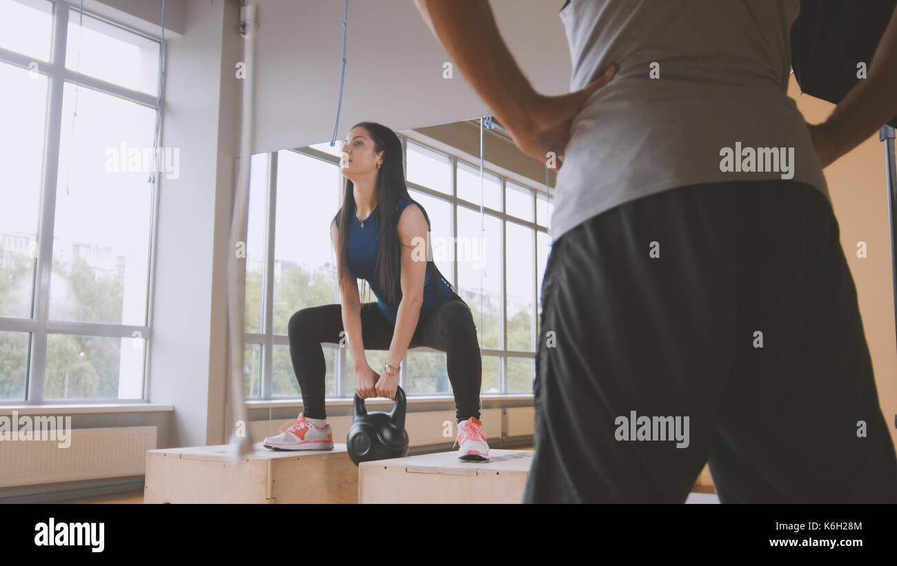 Woman working out doing squats with weigh in the gym - Stock Image