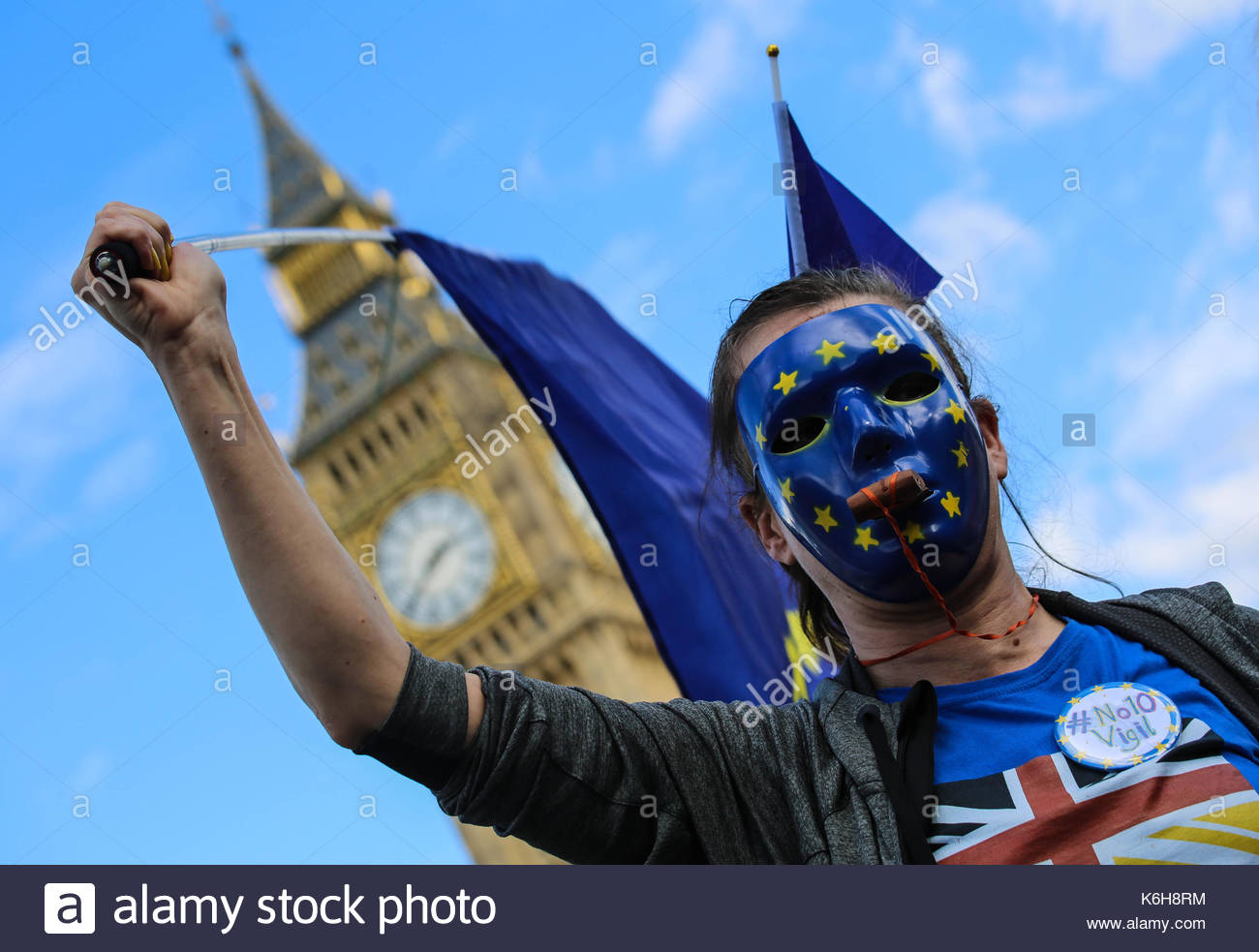 A masked anti-Brexit pro-EU supporter waves a blue flag at a rally in Central London which was held to protest against the whole Brexit process - Stock Image