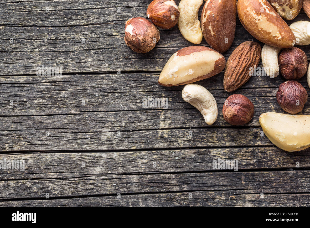Different types of nuts. Hazelnuts, walnuts, almonds, brazil nuts and pistachio nuts on old wooden table. - Stock Image