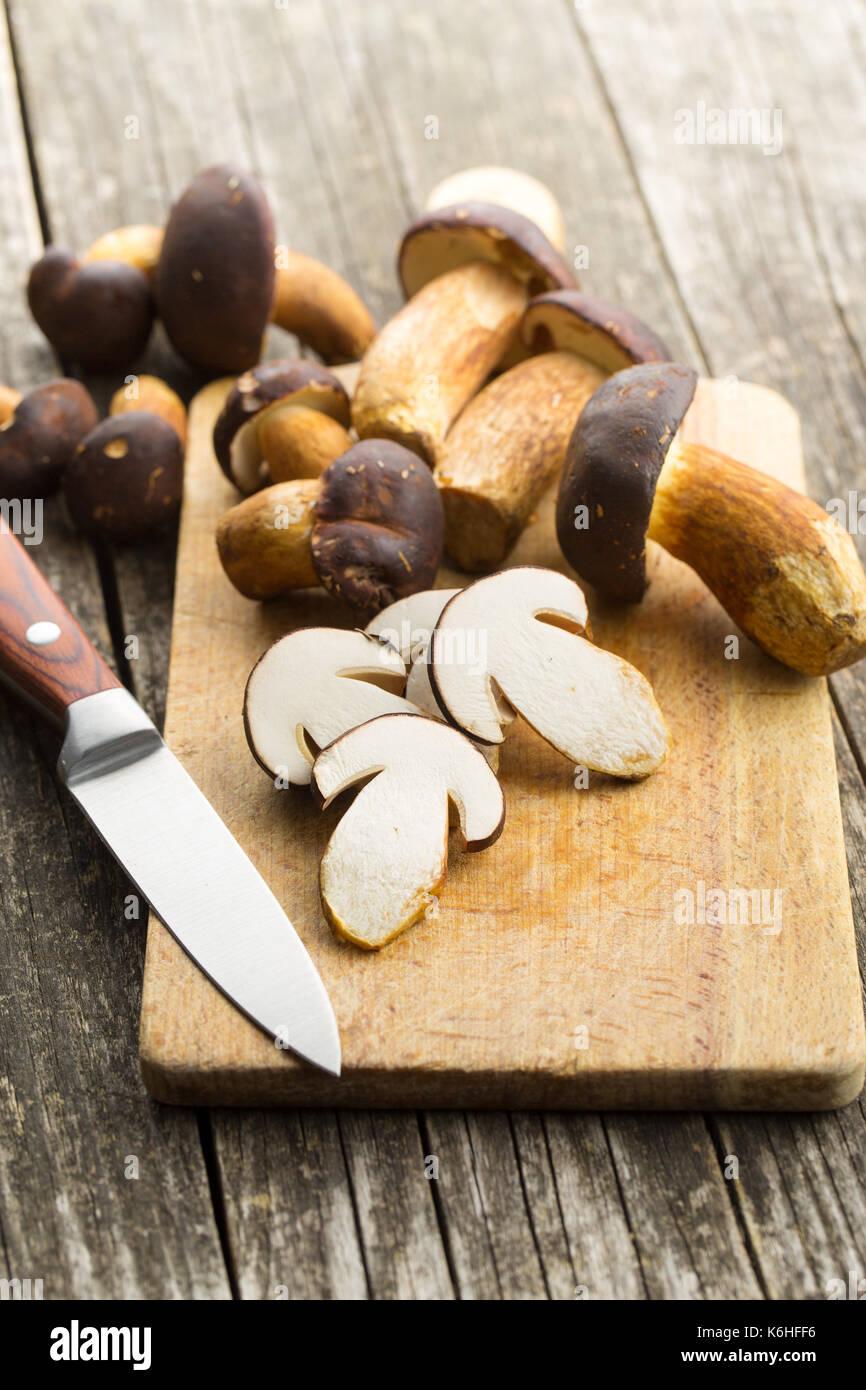 Sliced boletus mushrooms on cutting board and knife. Tasty food mushrooms. - Stock Image
