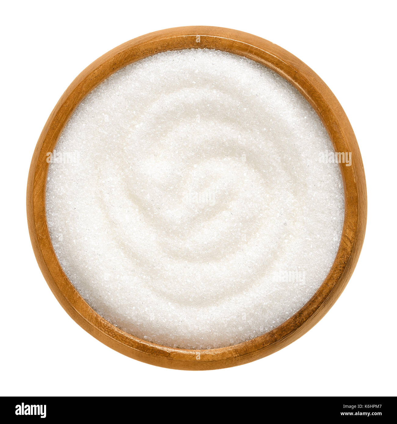 Fine granulated white sugar in wooden bowl. Crystals of refined table sugar. Sweet soluble carbohydrates. Sucrose. Macro photo. - Stock Image