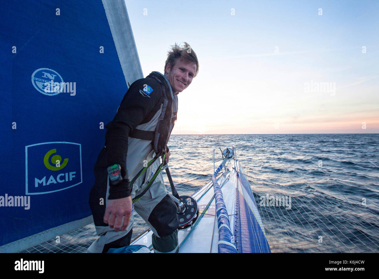 Sailor at bow of middle hull onboard trimaran, Atlantic Ocean, Brittany, France - Stock Image