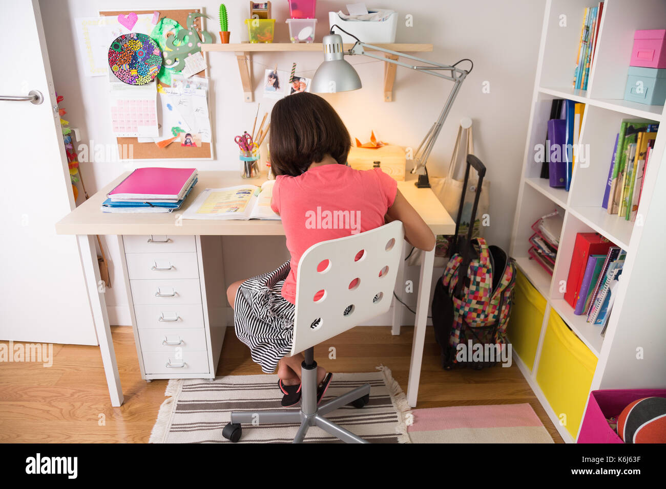 School girl doing homework at home in her desk. Back view. Stock Photo