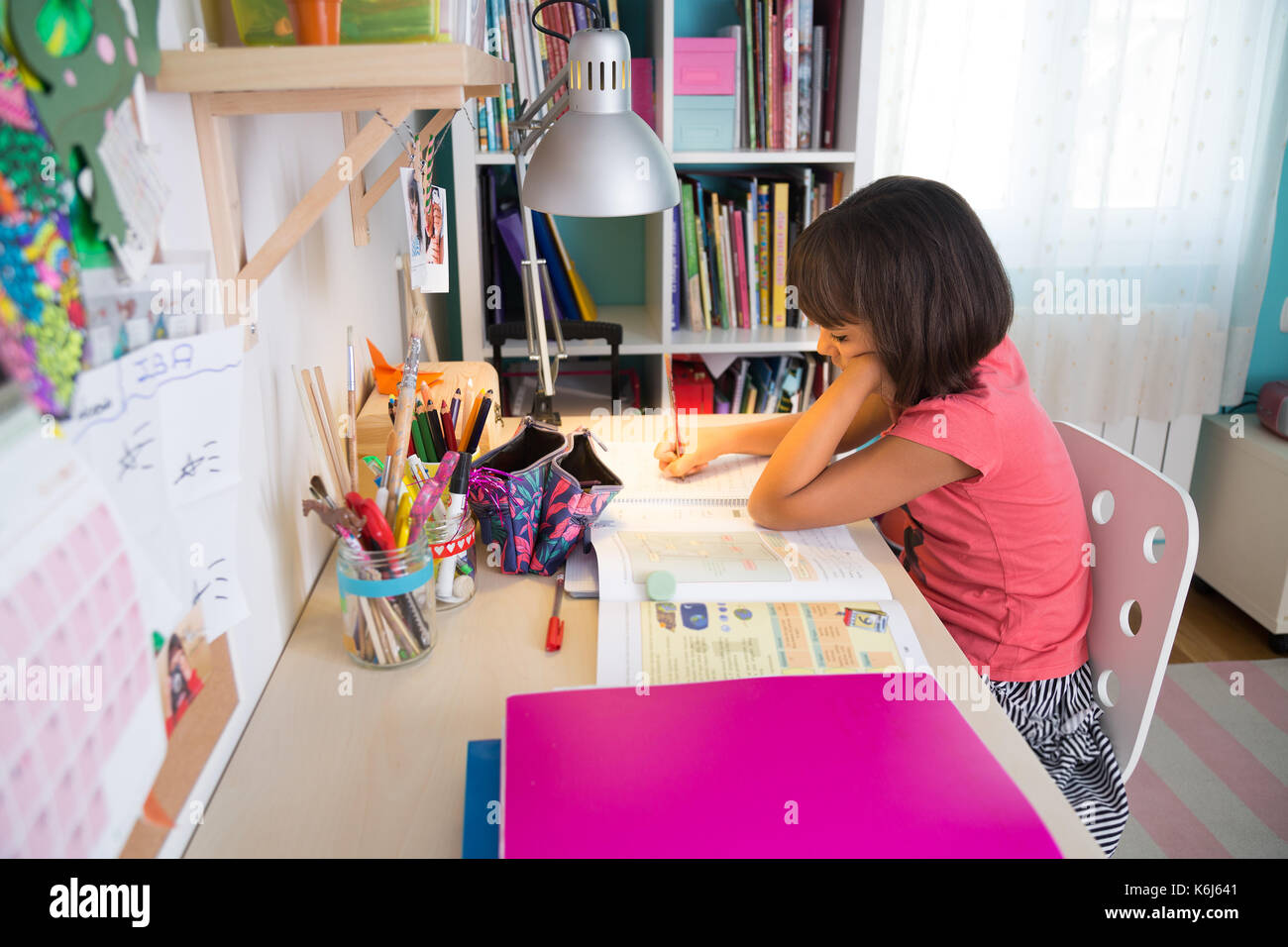 School girl doing homework at home in her desk - Stock Image