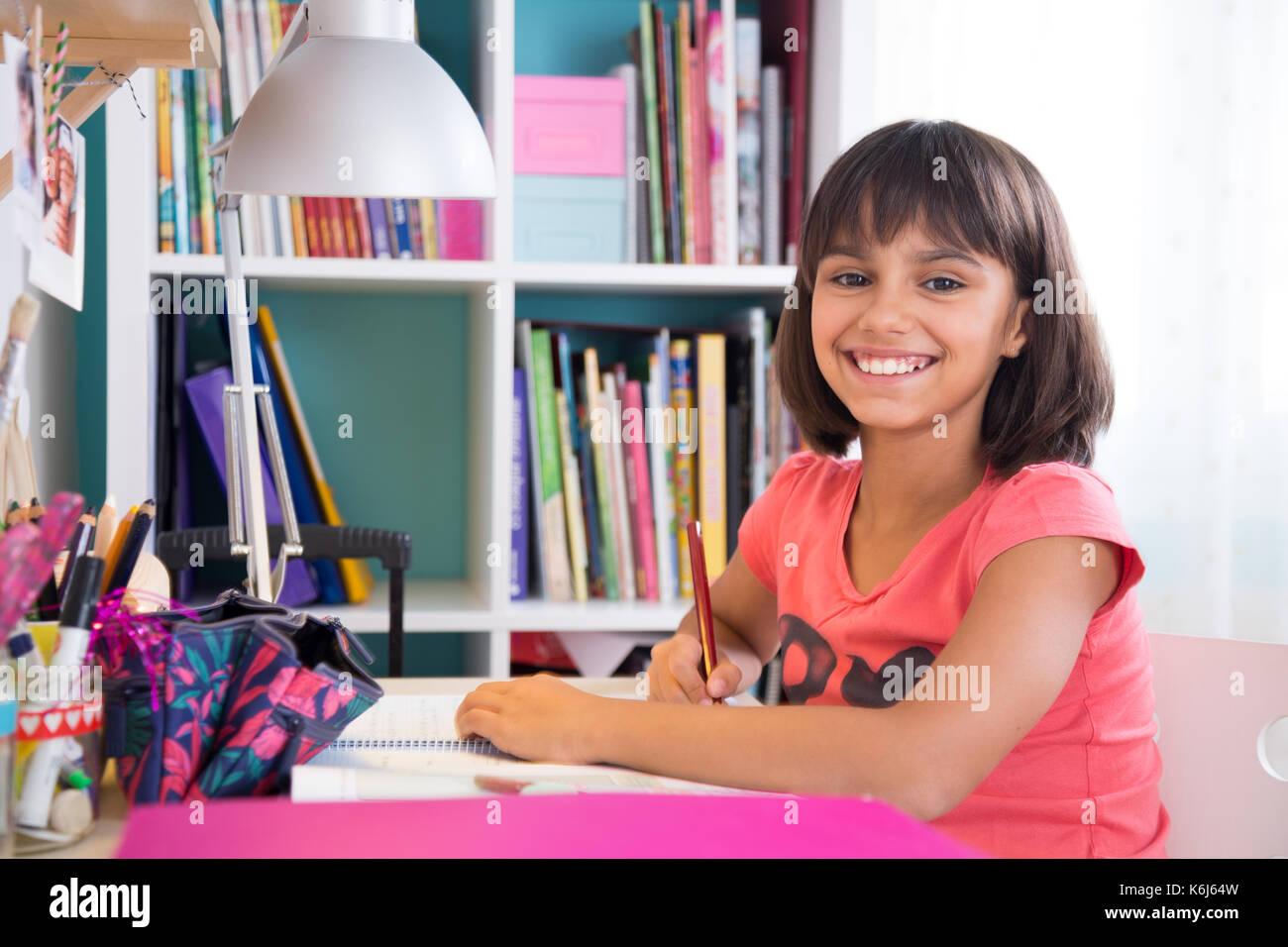 Cute happy school girl doing homework at home - Stock Image
