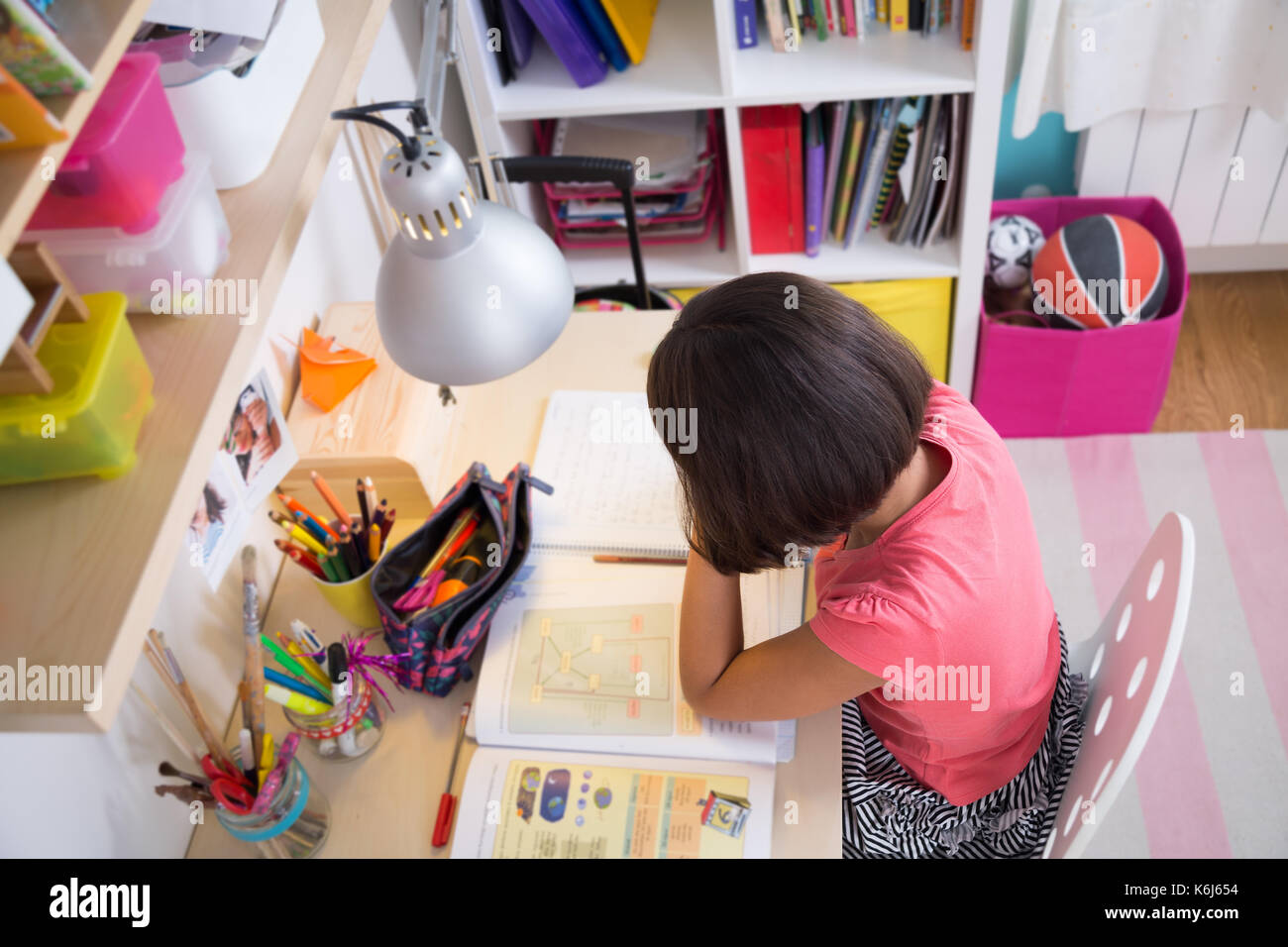 School girl doing homework at home in her desk. Top view Stock Photo