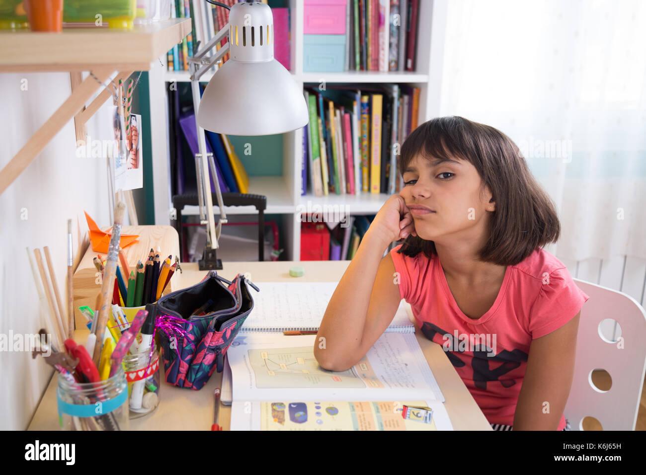 Bored school girl doing homework at home. Looking at camera - Stock Image