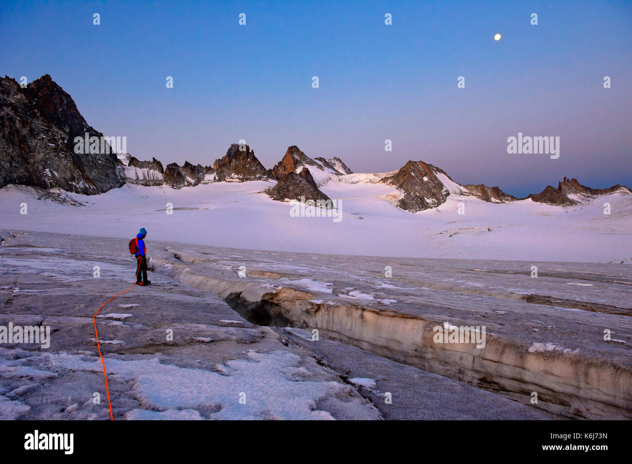 Alpinist at a crevasse on the glacier Plateau du Trient at full moon, Valais, Switzerland - Stock Image
