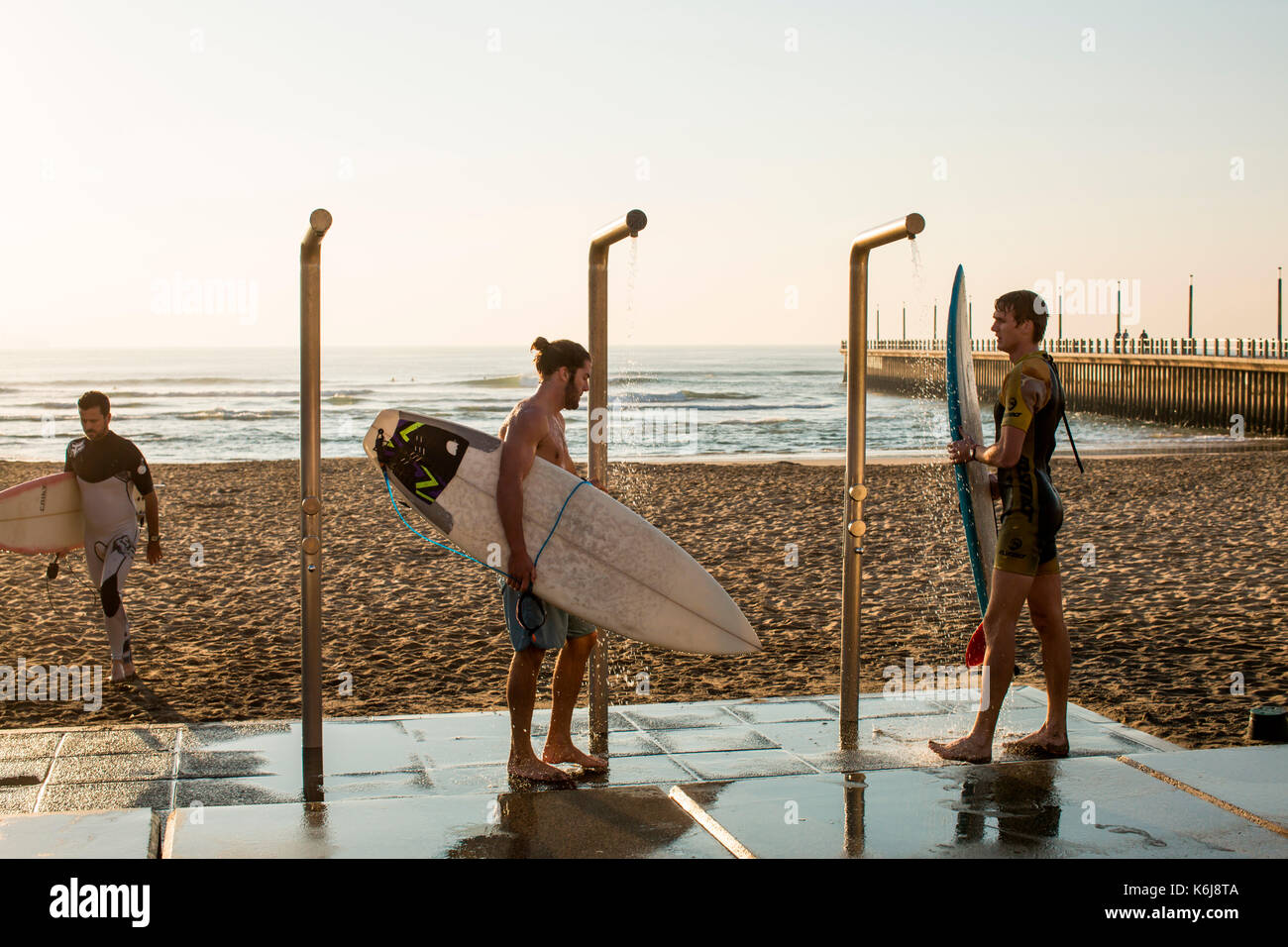 Men washing down surfboards near promenade on Golden Mile in Durban, South Africa - Stock Image