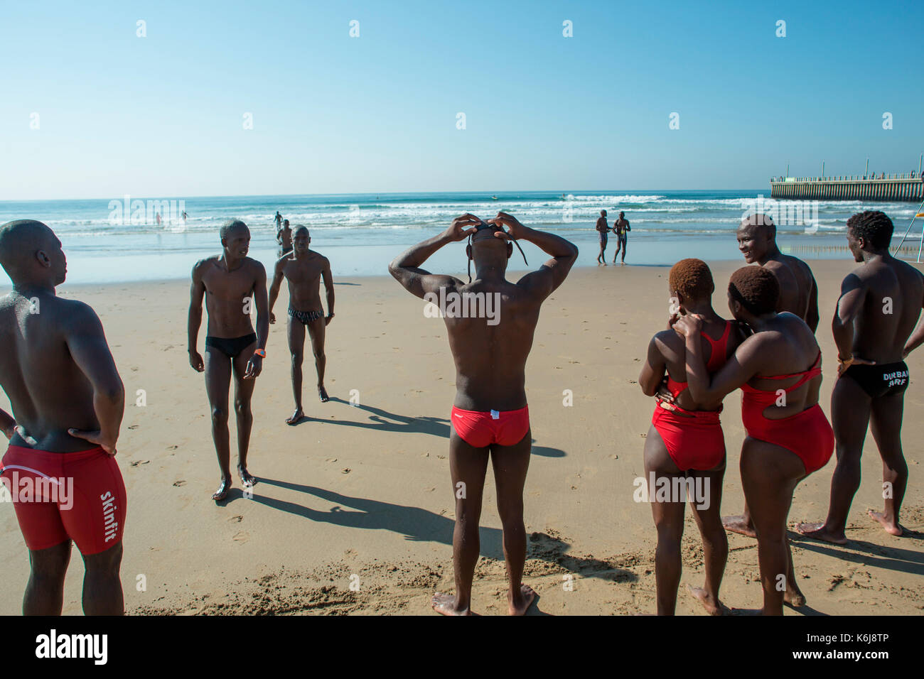 Lifeguards resting while performing training drills near promenade on Golden Mile, Durban, South Africa - Stock Image