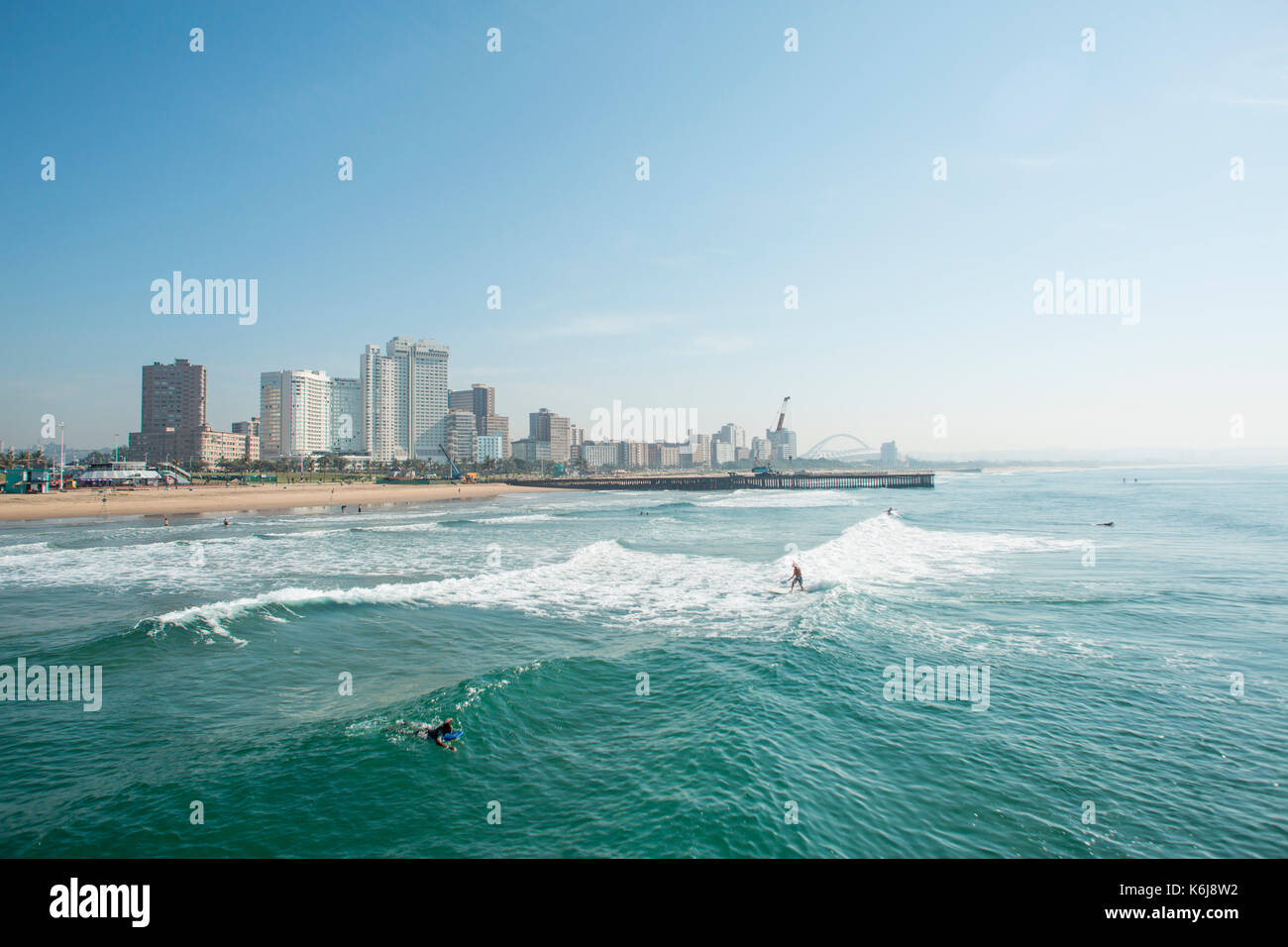 Surfers riding waves near pier on Golden Mile with skyline of Durban, South Africa - Stock Image