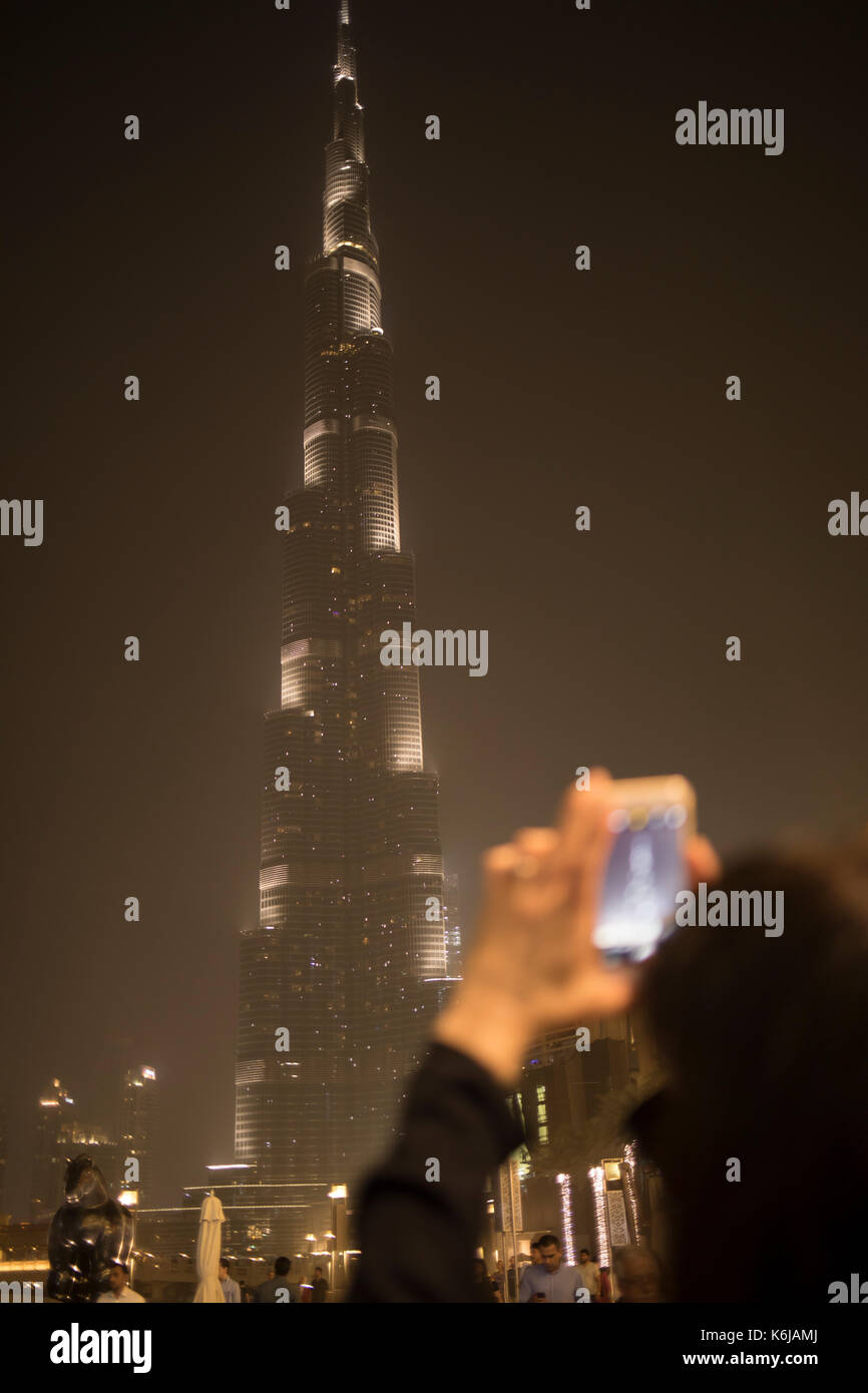 Woman capturing photos of Burj Khalifa in Dubai - Stock Image