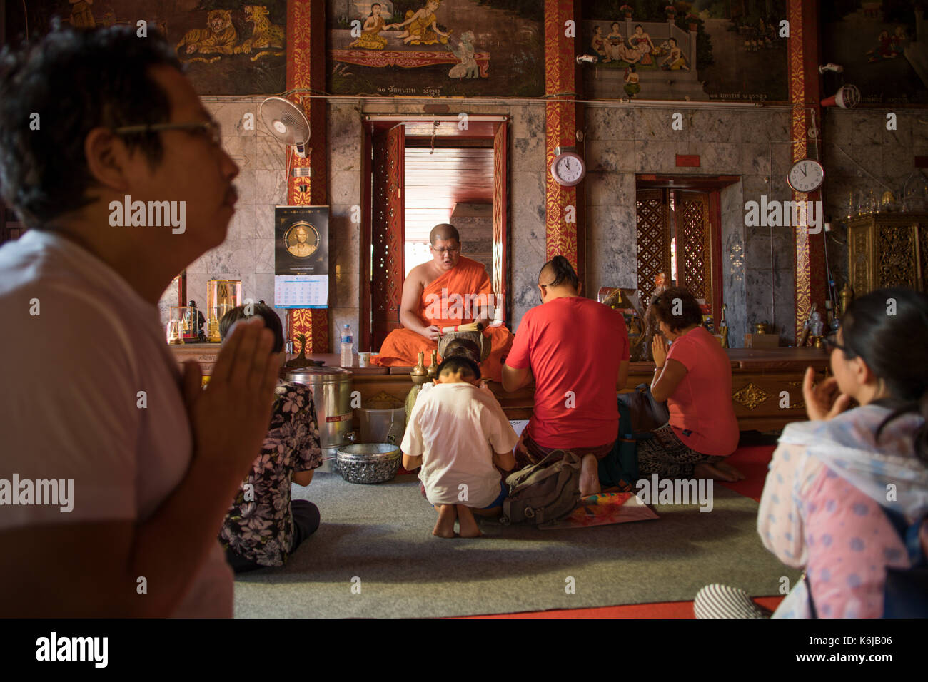 Buddhist monk blessing family at Wat Phra That Doi Suthep, Chiang Mai, Thailand - Stock Image