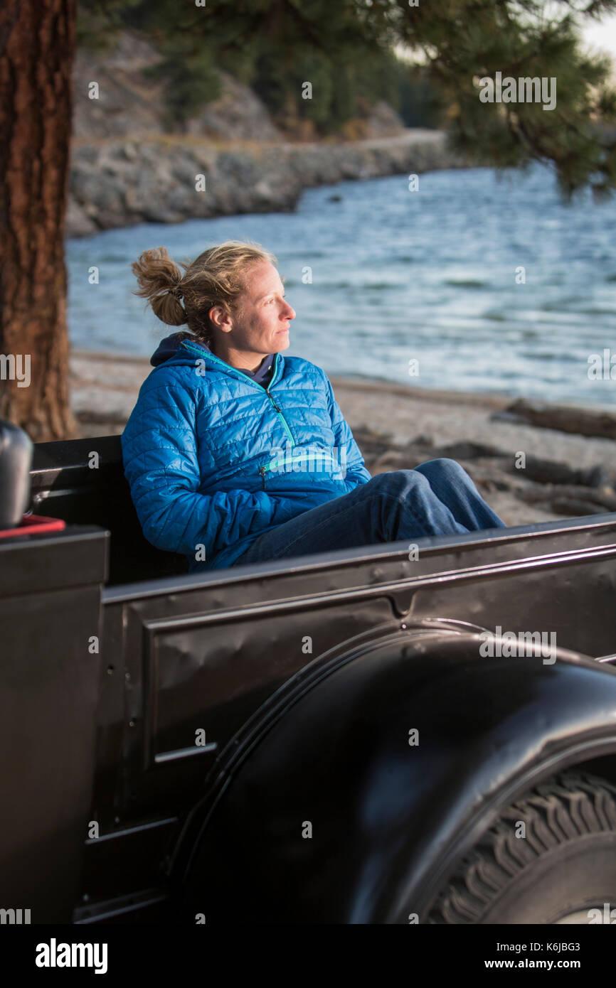 Woman sitting in renovated truck watching sunset, Payette Lake, McCall, Idaho, USA - Stock Image