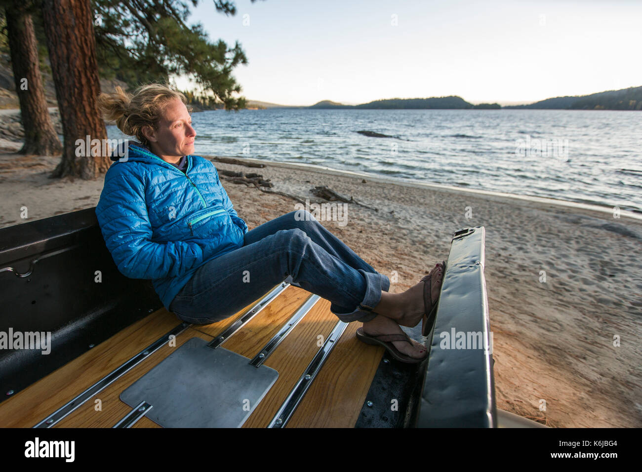 Woman sitting in renovated truck watching sunset, Payette Lake, McCall, Idaho, USA - Stock Image