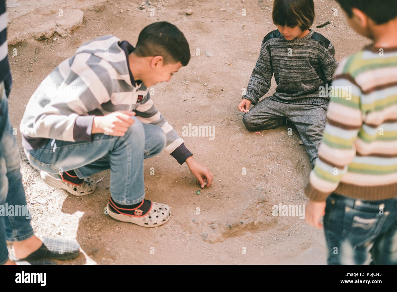 Westerner boy playing marbles in street with Moroccan kids, Marrakesh, Morocco - Stock Image