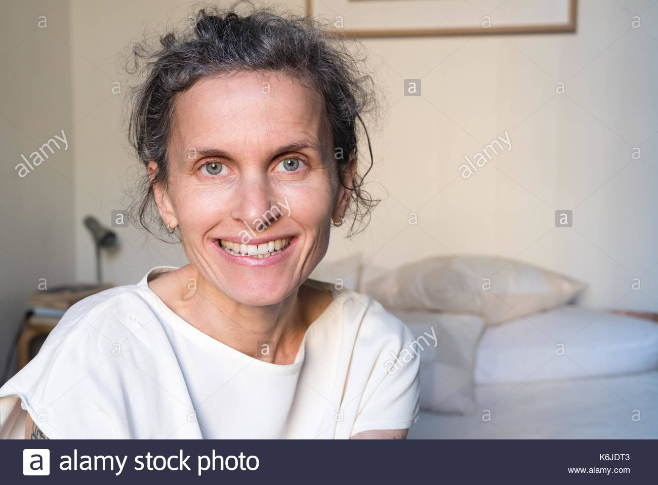 Portrait of happy smiling natural looking middle aged woman in bedroom (selective focus) - Stock Image