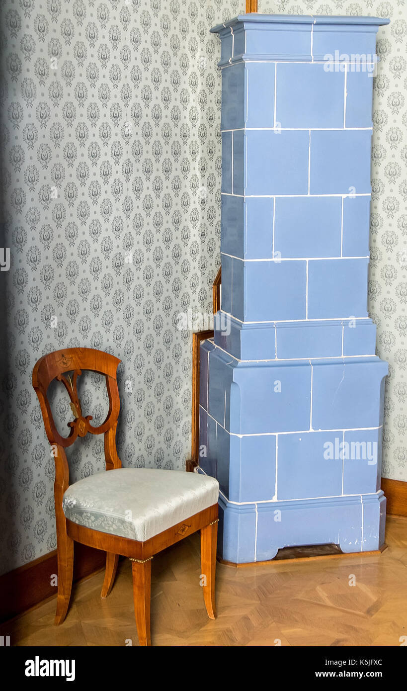 Historic tiled stove in the corner of the hall with a decorative upholstered chair. - Stock Image