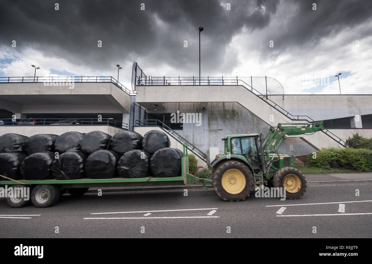 Yeovil, England, UK - July 17, 2010: A tractor towing a trailor of hay bales is incongruous against the urban backdrop of the Quedam shopping centre m - Stock Image