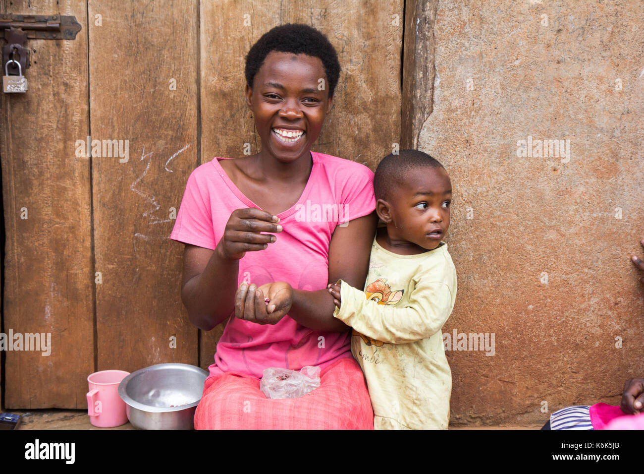 Lugazi, Uganda. 09 June 2017. A laughing African mother with a little child boy. The woman is sitting on door threshold sorting grains. - Stock Image