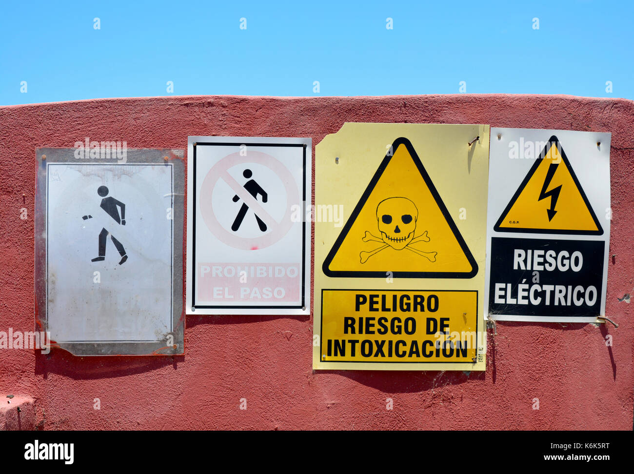 Photo of a set of warning signs for chemical and electrical dangers, written in  Spanish outside an industrial agricultural Stock Photo