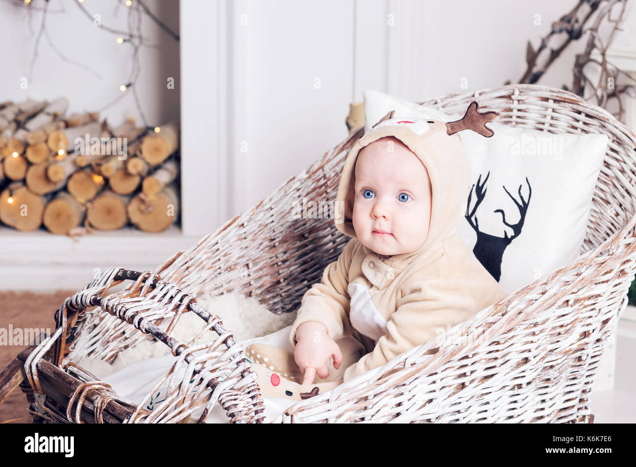 Christmas morning. Little girl in jumpsuit deer sitting in a toboggan. - Stock Image