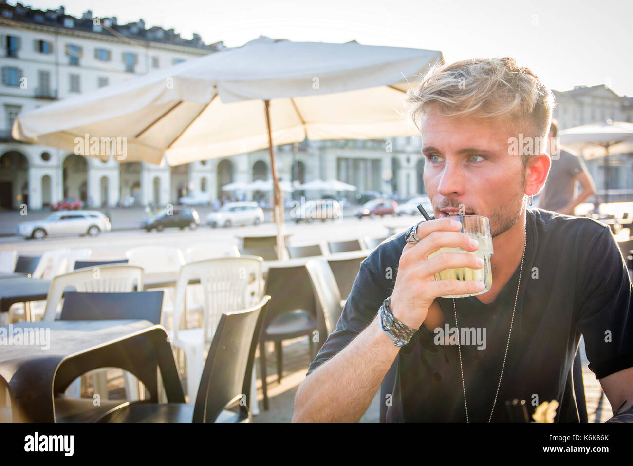 Handsome man sitting in cafe holding glass - Stock Image