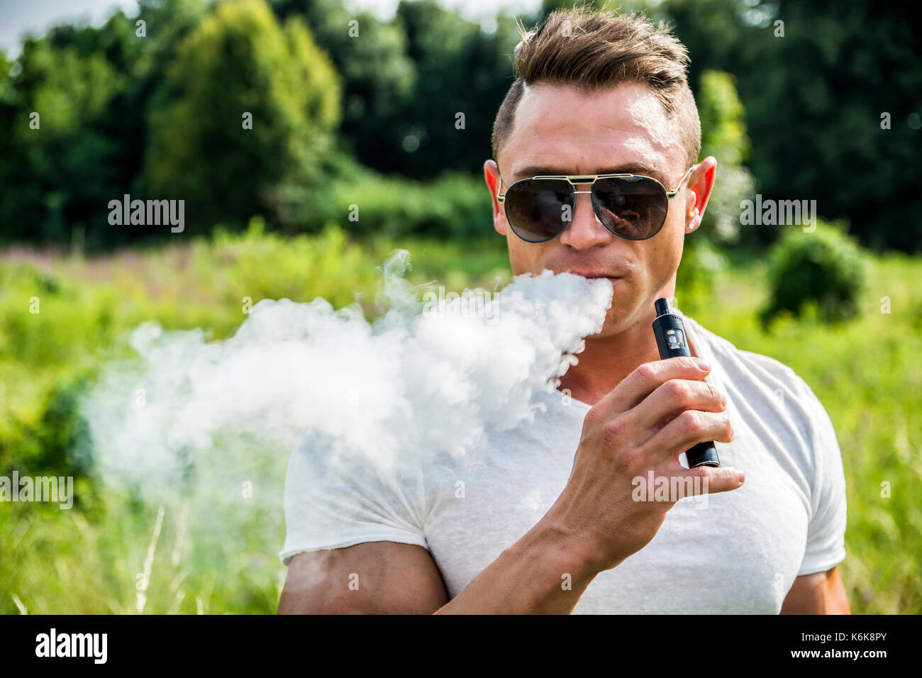 Man smoking ecig in nature - Stock Image