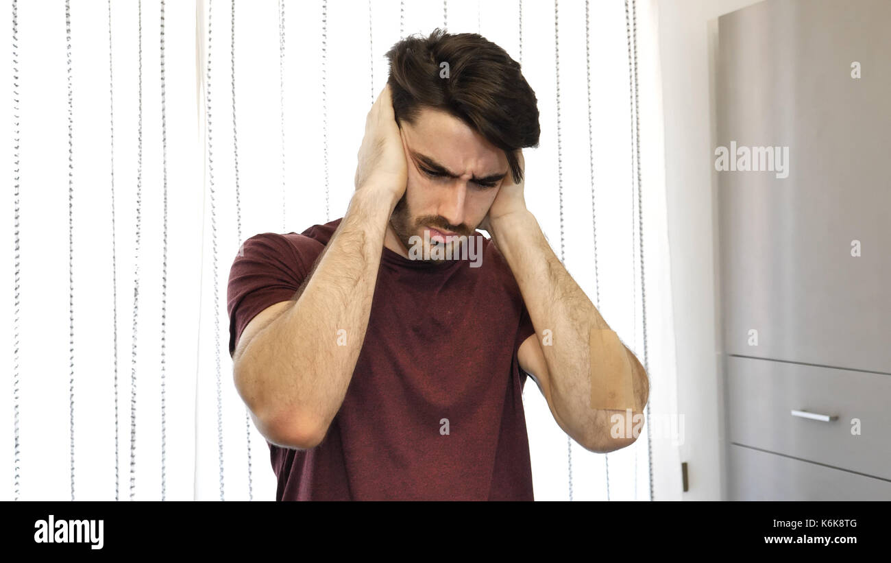 Young man covering his ears, too much noise - Stock Image
