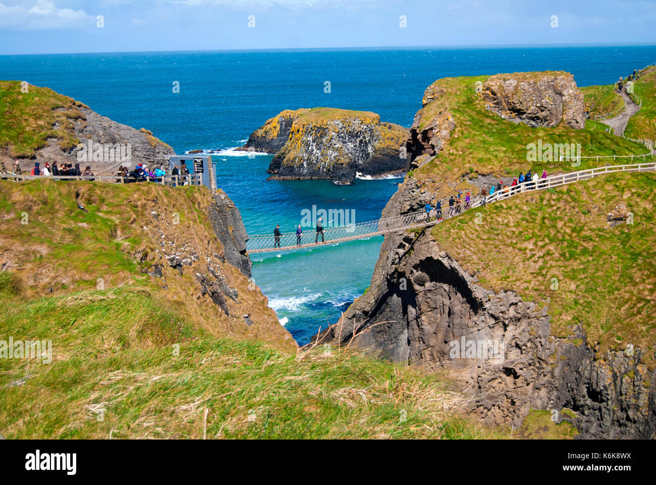 Ballintoy, United Kingdom - May 2, 2016: Carrick-a-Rede Rope Bridge, a popular tourist destination in Northern Ireland. Tourists passing the bridge. - Stock Image