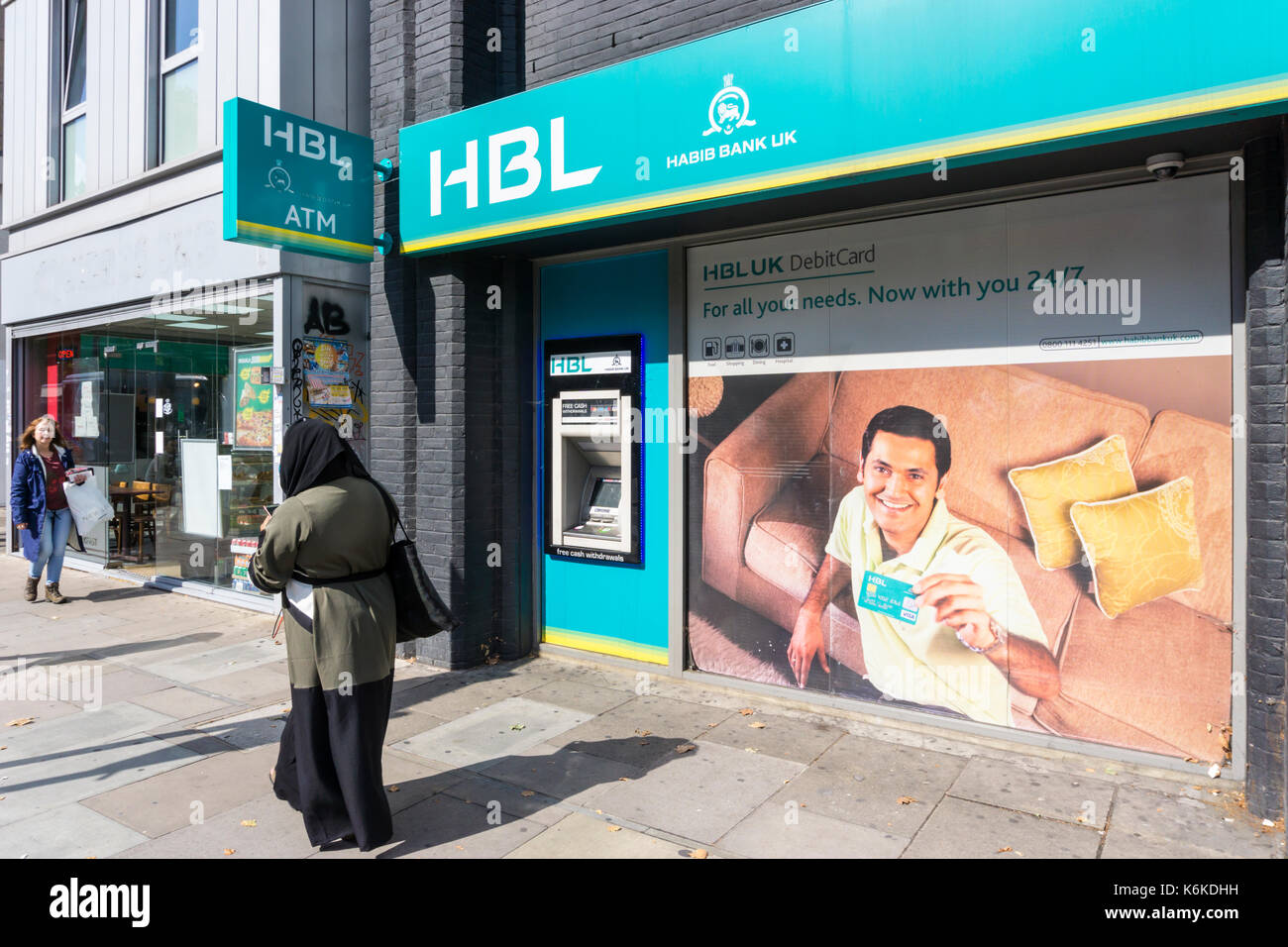 A woman wearing a hijab walks past a branch of the Pakistan based Habib Bank UK and HBL ATM in Whitechapel Road, London. - Stock Image