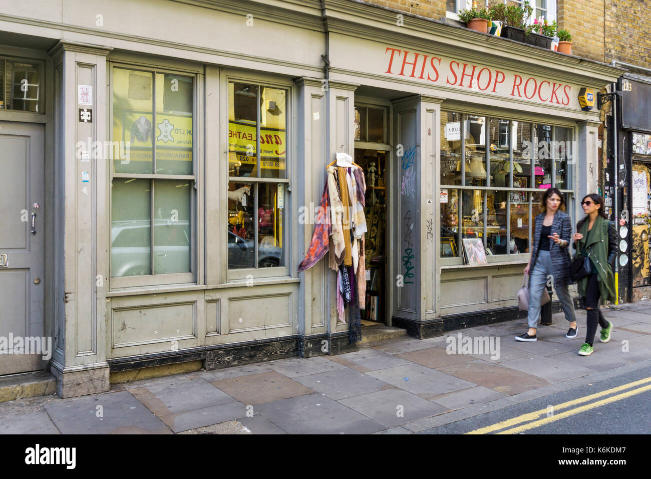Two woman walking past This Shop Rocks secondhand clothing, furniture and book shop in Brick Lane, London - Stock Image