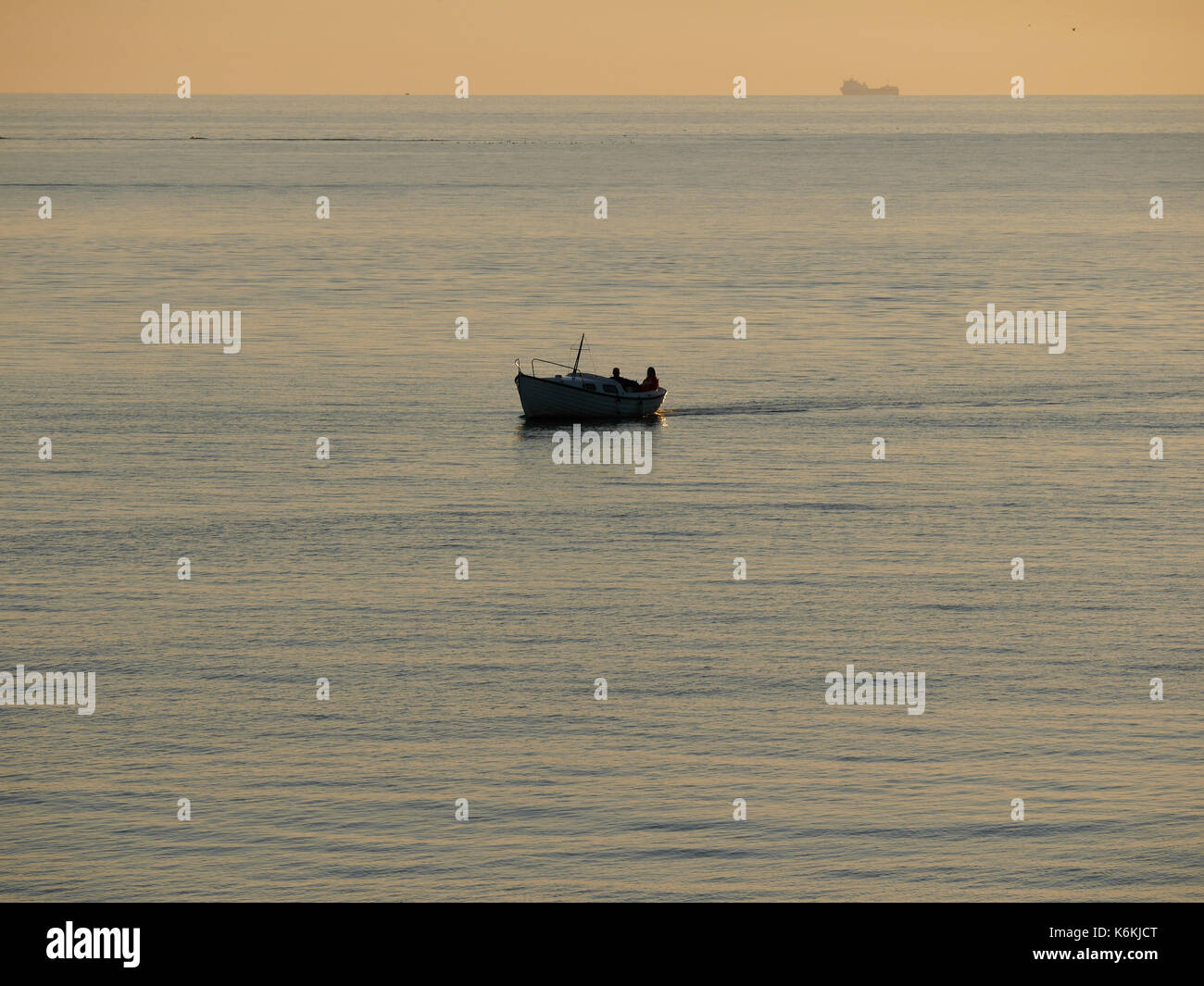 Sunset at Hönö, Klåva in the archipelago of Gothenburg. Boat with two persons on passing by, freight ship in the background. Stock Photo